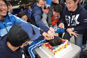 ホンダドライバーたちによって、抵抗虚しくケーキに押しつけられた小暮卓史