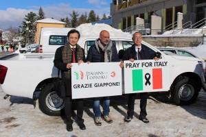 『PRAY FOR ITALY』、『GRAZIE GIAPPONE(ありがとう日本)』のボードとともにたつピロッツィ市長、在イタリア日本大使館の山内弘志次席公使、ITALIANS for TOHOKUとPRAY FOR ITALYの事務局長を務める服部浩巳さん