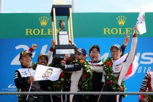 """優勝を喜ぶ8号車トヨタの中嶋一貴、ブエミ、アロンソ、村田チーム代表、友山GRカンパニープレジデント。表彰台には""""モリゾウ""""が描かれたフラッグも登場した。"""